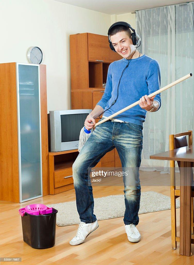 Hombre feliz lavado piso de madera con mop : Foto de stock