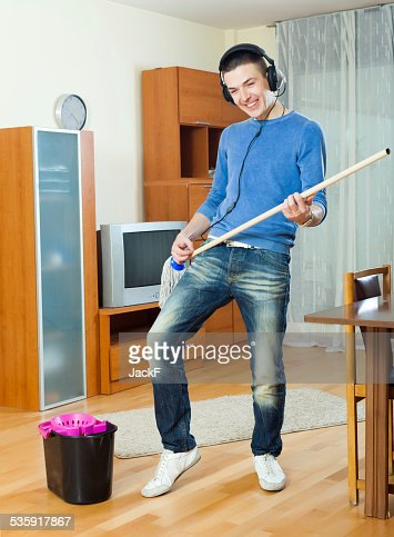 Happy man washing parquet floor with mop : Stock Photo