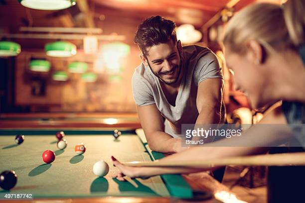 Happy man watching his girlfriend playing snooker in pool hall.