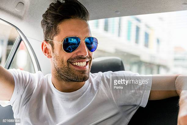 Happy man wearing sunglasses in car