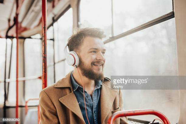 Happy man with a bright smile on his face listening to music on a public transport