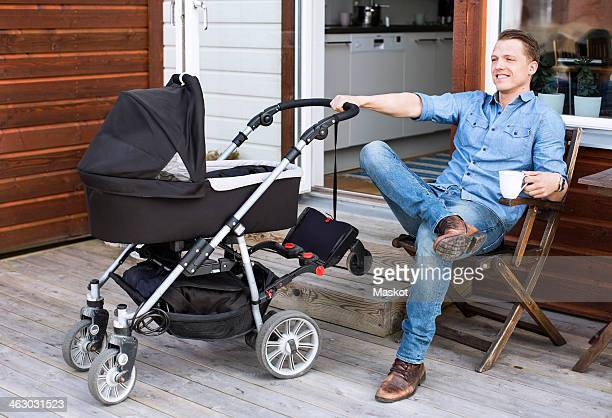 Happy man with baby carriage holding coffee mug while sitting at patio