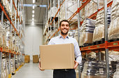 wholesale, logistic, business, export and people concept - happy man with cardboard parcel box at warehouse