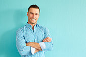 Happy handsome man with crossed arms leaning against a turquoise wall