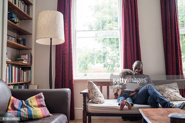 ハッピーな男性、娘を使用して、デジタルタブレットのソファー
