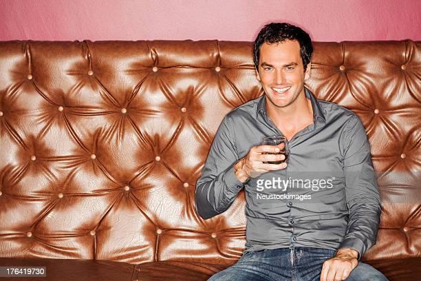 Happy Man With Drink Sitting On Sofa At Nightclub