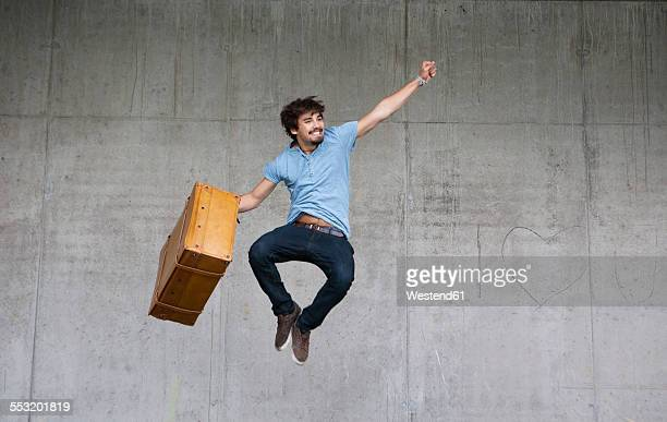 Happy man with leather suitcase jumping in the air