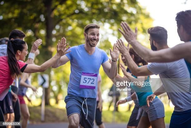 Happy marathon runner greeting group of athletes at finish line.