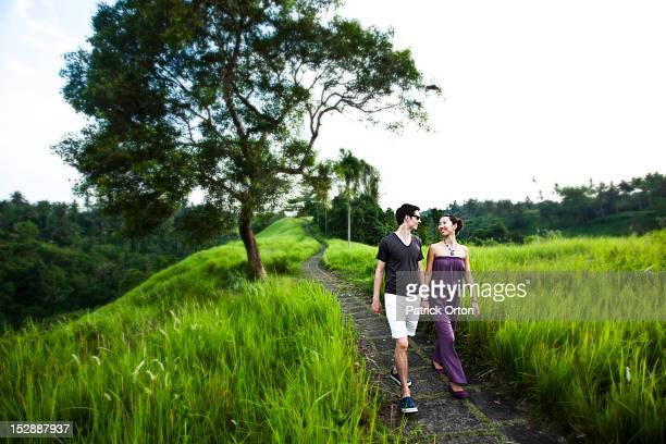 A happy married couple holding hands and walking in a lush jungle setting in Bali, Indonesia.