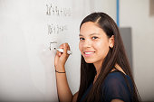 Beautiful Hispanic student writing on a white board at school and smiling