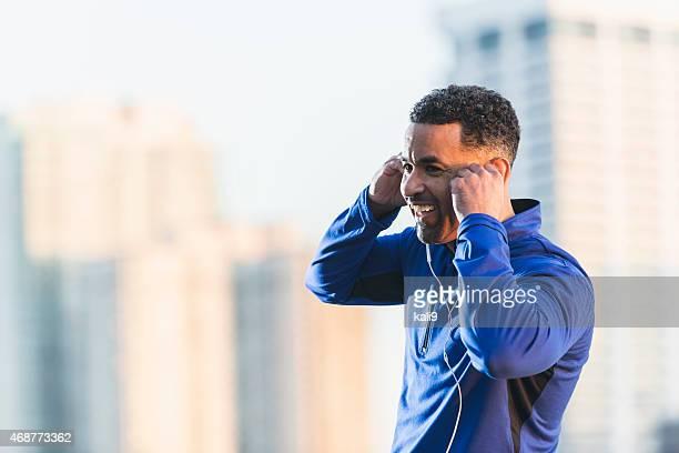 幸せな成熟したブラックの男性のスポーツウェアに earbuds