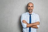 Happy mature businessman in blue shirt and tie looking at camera. Portrait of smiling and satisfied hispanic business man with arms crossed isolated over grey background with copy space. Successful se