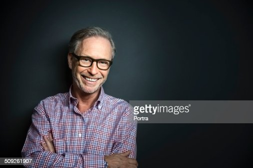 Happy mature businessman standing arms crossed