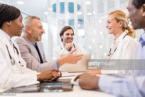 Happy mature businessman talking on a meeting with doctors.
