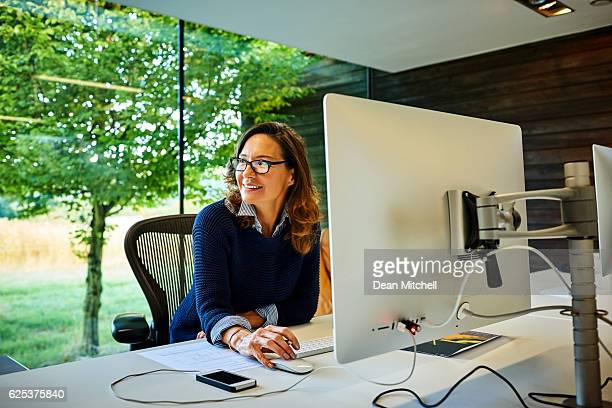 Happy mature businesswoman sitting at her desk