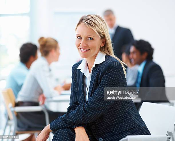 Happy mature businesswoman with colleagues in the background