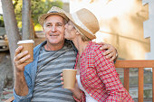Happy mature couple drinking coffee on a bench in the city on a sunny day