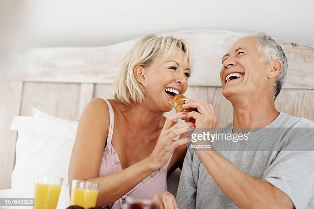 Happy mature couple enjoying their breakfast in bed