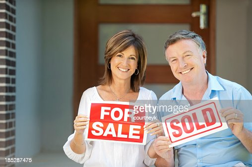 Happy mature couple holding for sale and sold signs