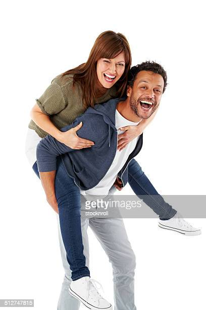 Happy mature couple piggybacking on white