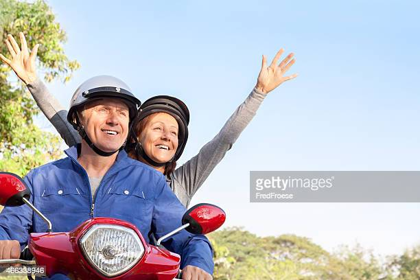 Happy Mature Couple Riding a Motor Scooter