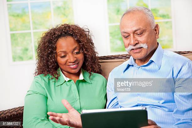 Happy mature couple share information, video chats on digital tablet.