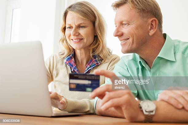 Happy mature couple shopping online