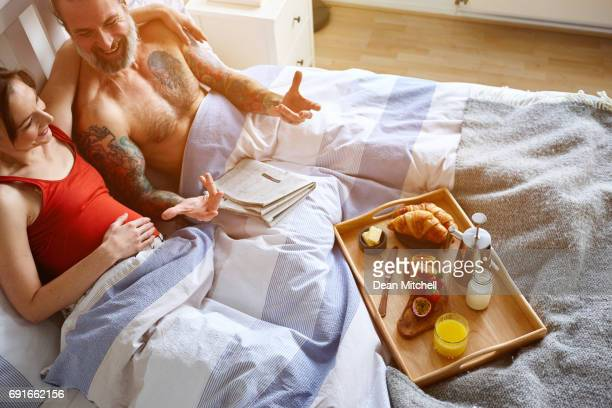Happy mature couple sitting on bed and talking