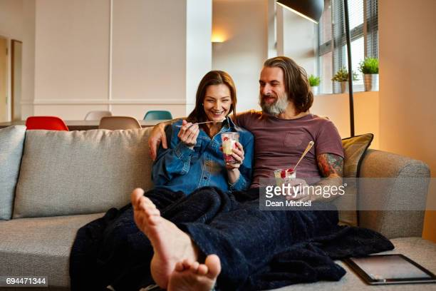 Happy mature couple sitting on sofa and eating ice cream.