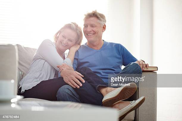 Happy mature couple sitting together on couch