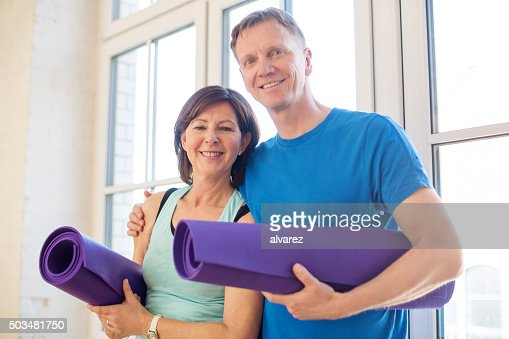 Happy mature couple standing with yoga mats