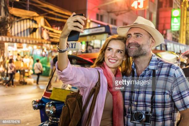 Happy Mature Couple Taking Chinatown Selfies on Vacation in Bangkok