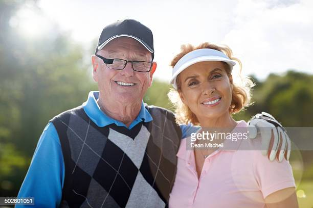 Happy mature couple together at golf course
