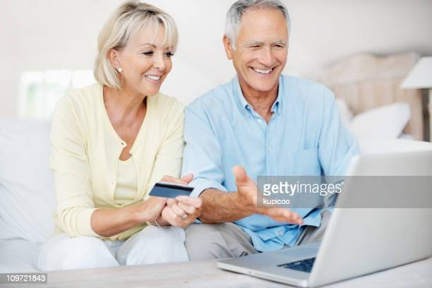 Happy mature couple using credit card to shop online