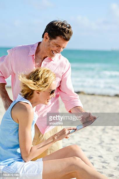 Heureux Couple d'âge mûr à l'aide de tablette numérique sur la plage