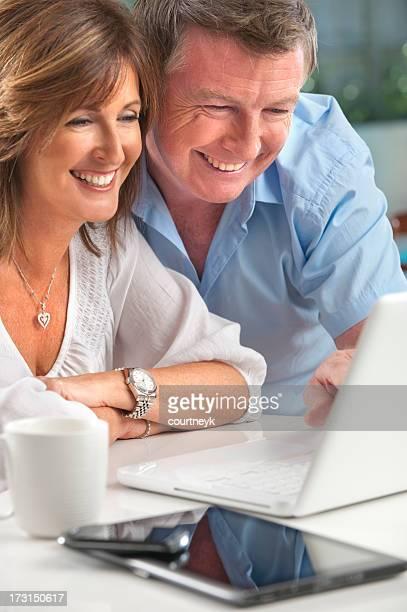 Happy mature couple using wireless technology