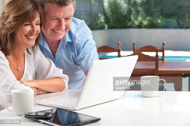 Happy mature couple using wireless technology