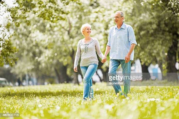 Happy mature couple walking in the field.
