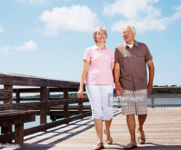 Happy, mature couple walking on a pier