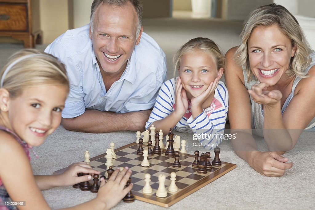 Happy mature couple watching kids play chess at home : Stock Photo