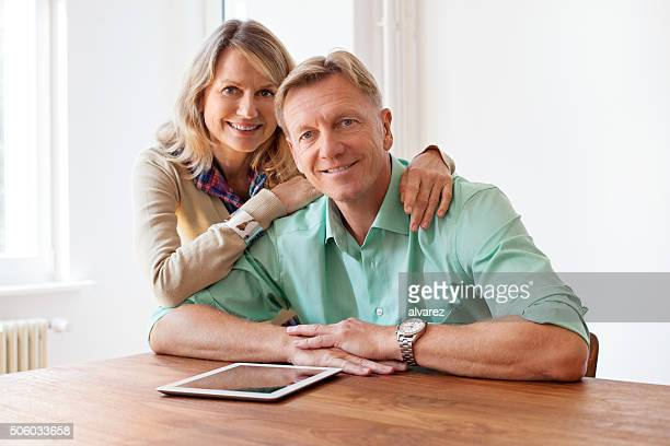 Happy mature couple with digital tablet at home