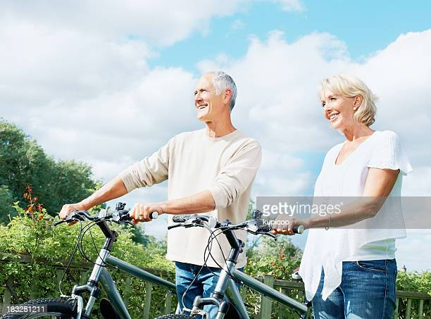 Happy mature couple with their bicycles in the countryside