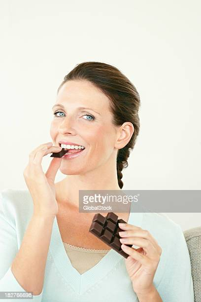 Happy mature female enjoying a bar of dark chocolate