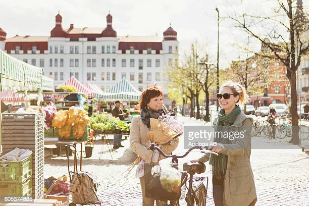 Happy mature female friends with bicycle after shopping at market
