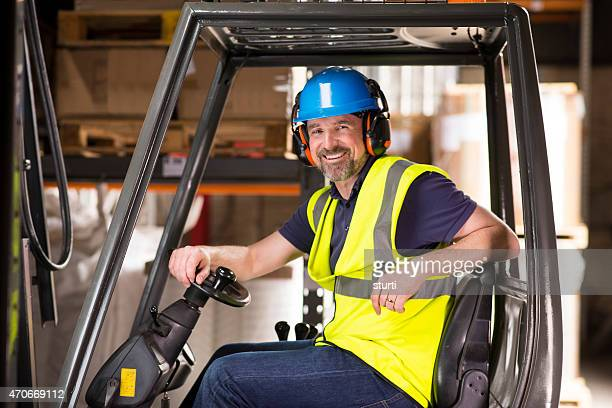 happy mature forklift truck driver smiling to camera