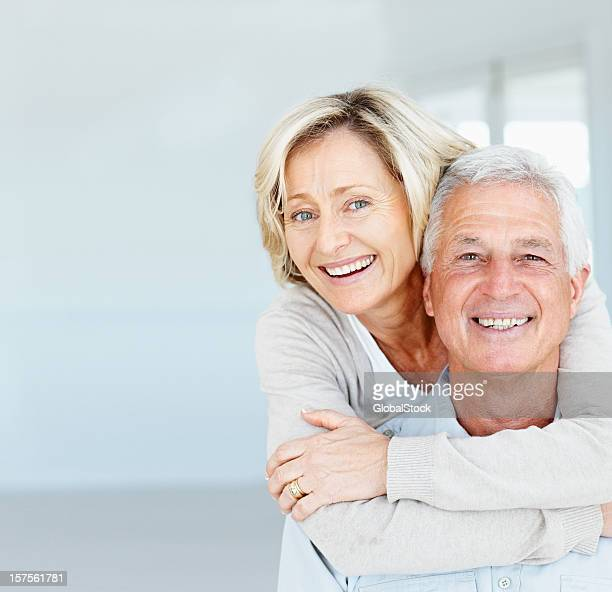Happy mature lady hugging her husband from behind
