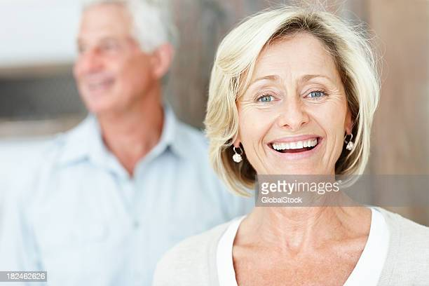 Happy mature lady with husband in the background