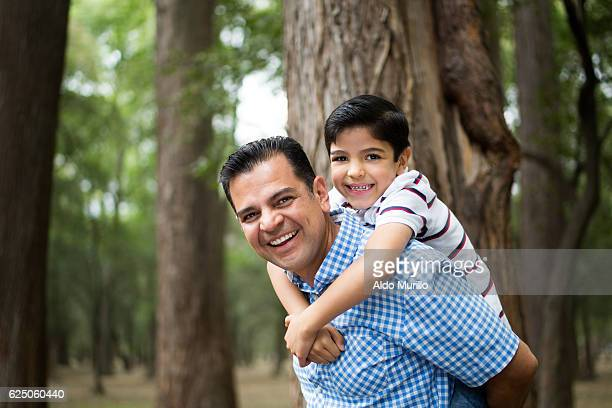 Happy mature latin father carrying son on back