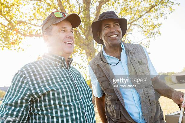 Happy mature male friends prepare to fish together