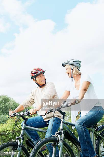 Happy mature man and woman on cycle ride in countryside